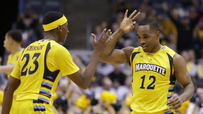Marquette's Derrick Wilson and JaJuan Johnson celebrate during the second half of an NCAA college basketball game against North Dakota on Monday, Dec. 22, 2014, in Milwaukee. (AP Photo/Aaron Gash)