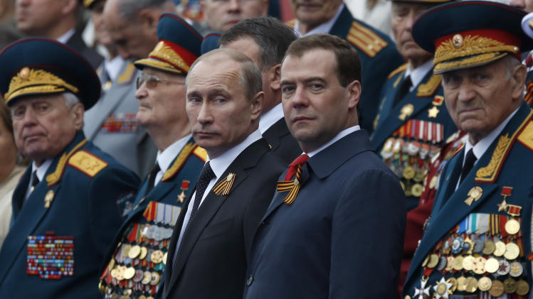 Russian President Vladimir Putin, center left, and Prime Minister Dmitry Medvedev, center right, and a group of Russian WWII veterans watch the Victory Day Parade, which commemorates the 1945 defeat of Nazi Germany on the Red Square in Moscow,  Russia, Wednesday, May 9, 2012.Russian President Vladimir Putin has told the annual massive military parade in Red Square that the country will stand up for its positions.(AP Photo/Alexander Zemlianichenko)