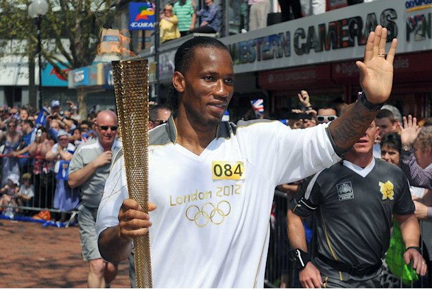 This photograph made available by LOCOG shows Didier Drogba carrying the Olympic Flame on the leg between Royal Wootton Bassett and Swindon, south west England, Wednesday May 23, 2012. The Olympic tor