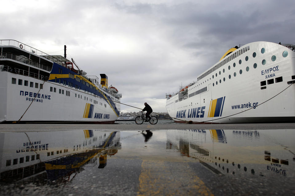 A man on a bicycle passes docked ferries in the port of Piraeus, near Athens, during a 24 hour strike on Tuesday, Feb. 7, 2012. Unions have called a 24-hour general strike for Tuesday, in response to the new austerity measure. (AP Photo/Petros Giannakouris)