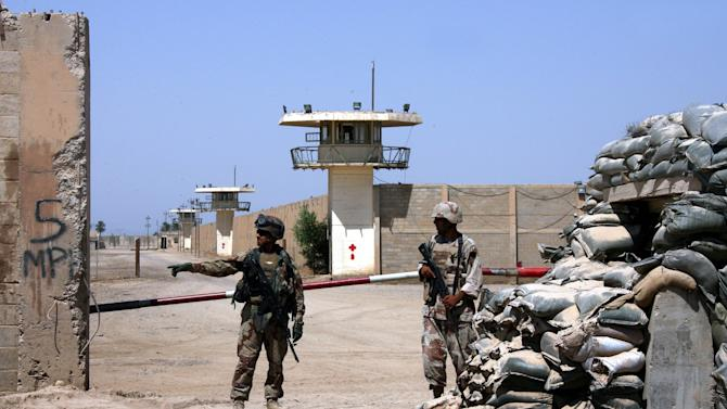 FILE - In this Sept. 2, 2006, file photo, Iraqi army soldiers stand guard at the Abu Ghraib prison, after taking over from U.S. soldiers, on the outskirts of Baghdad, Iraq. A defense contractor whose subsidiary was accused in a lawsuit of conspiring to engage in torture at the infamous Abu Ghraib prison in Iraq has paid $5.28 million to 71 former inmates held there and at other U.S.-run detention facilities between 2003 and 2007. The settlement in the case involving Engility Holdings Inc. of Chantilly, Va., marks the first successful effort by lawyers for former prisoners at Abu Ghraib and other detention centers to collect money from a U.S. defense contractor in lawsuits alleging torture. Another contractor, CACI, is expected to go to trial over similar allegations this summer. (AP Photo/Khalid Mohammed, File)
