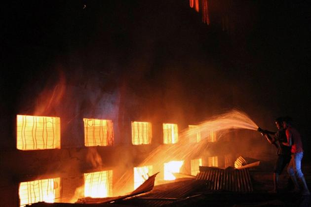 This picture taken on 24 November, 2012 shows Bangladeshi people and firefighters trying to extinguish a fire in a garment factory in Savar, 30 kilometres north of Dhaka. The death toll from a fire at