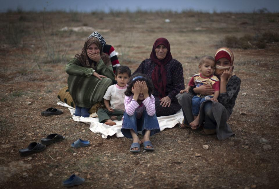A Syrian family who fled from the violence in their village sit on the ground at a displaced camp in the Syrian village of Atmeh, near the Turkish border with Syria, Thursday, Nov. 8, 2012.(AP Photo/ Khalil Hamra)