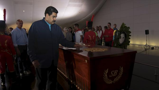 Venezuela's President Maduro places his hand on the tomb of national hero Simon Bolivar during an event with the Revolutionary Youth at the National Pantheon in Caracas