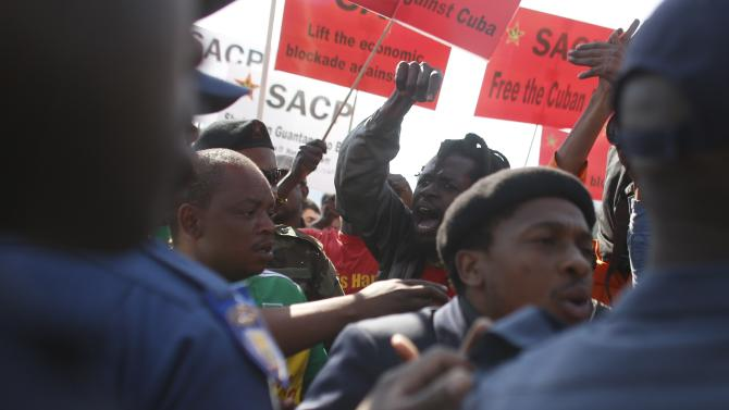 Police officers push back protesters during a demonstration against the upcoming visit of United States President at the university in Soweto near the university in Soweto, South Africa, Saturday June 29, 2013. Mandela remains in critical condition in a Pretoria hospital as U.S. President Barack Obama visit South Africa as the second leg of his African visit. (AP Photo/Markus Schreiber)