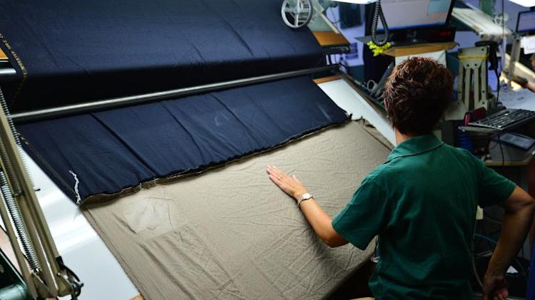A woman works at Italian fashion group Loro Piana's plant in Roccapietra on September 9, 2013