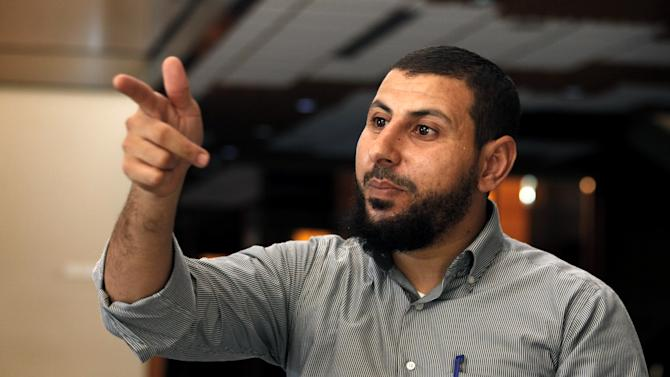 "Youssef Jihani, senior member of Ansar al-Shariah Brigades, speaks to the Associated Press during an interview, in Benghazi, Libya, Tuesday, Sept. 18, 2012. Ansar al-Shariah is among the most powerful of the many, heavily armed militias that the government relies on to keep security in Benghazi. Jihani, denied the group took part in the attack. ""We never approve of killing civilians, especially those who helped us,"" he said the day after the attack. (AP Photo/Mohammad Hannon)"