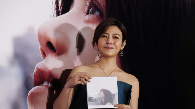 """FILE - In this Wednesday, May 8, 2013 file photo, Taiwanese singer-actress Michelle Chen poses with her new song album """"Me Myself and I"""" during a promotional event for the album in Hong Kong. Fans know her as the sweet schoolgirl in the 2011 blockbuster """"You Are the Apple of My Eye."""" Now, they can take a closer look at Michelle Chen through her first love: music. The 29-year-old actress said she poured her heart and soul into her first studio album, """"Me Myself and I."""" (AP Photo/Kin Cheung, File)"""