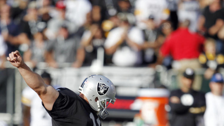 Oakland Raiders kicker Sebastian Janikowski, left, kicks a 43-yard field goal to win the game against the Pittsburgh Steelers during the fourth quarter of an NFL football game in Oakland, Calif., Sunday, Sept. 23, 2012. Oakland won 34-31. (AP Photo/Tony Avelar)