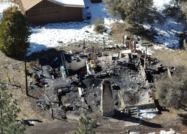 In this aerial photo, law enforcement authorities investigate the charred remains of a cabin Wednesday, Feb. 13, 2013, where quadruple-murder suspect Christopher Dorner is believed to have died after 