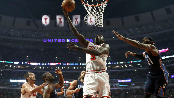 Chicago Bulls forward Luol Deng (9) shoots past Charlotte Bobcats forward Hakim Warrick (21) as Joakim Noah (13) watches during the first half of an NBA basketball game Monday, Dec. 31, 2012, in Chicago. (AP Photo/Charles Rex Arbogast)