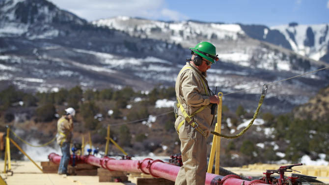 In this March 29, 2013 photo, a worker helps monitor water pumping pressure and temperature, at the site of a natural gas hydraulic fracturing and extraction operation run by Encana Oil & Gas (USA) Inc., outside Rifle, in western Colorado. Technology created an energy revolution over the past decade, but Old Energy is winning. Oil companies big and small have used technology to find a bounty of oil and natural gas so large that worries about running out have melted away.  (AP Photo/Brennan Linsley)