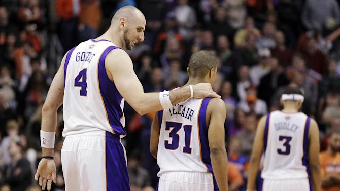 Phoenix Suns' Marcin Gortat (4), of Poland, walks with Sebastian Telfair (31) to the bench after Telfair turned the ball over during the second half of an NBA basketball game against the New York Knicks, Wednesday, Dec. 26, 2012, in Phoenix. The turnover gave the Knicks the game-winning shot on the next possession for a 99-97 victory. (AP Photo/Matt York)