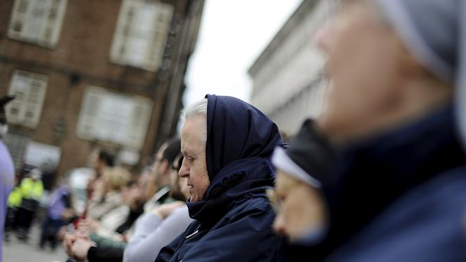 A faithful prays outside the Cathedral of Turin during a Mass to mark the opening of the Holy Shroud exposition