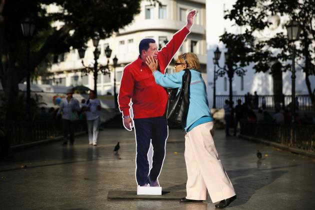 A woman touches a cardboard cut-out of late Venezuela's president Hugo Chavez at Plaza Bolivar in Caracas