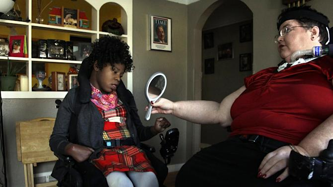 In this Nov. 14, 2012 photo, Carrie Ann Lucas, right, mother of four disabled adopted children, holds up a mirror for her daughter, Adrianne, 13, at their home in Windsor, Colo., before going on an outing. Carrie Ann Lucas herself uses a power wheelchair and is reliant on a ventilator due to a form of muscular dystrophy. In diverse and profound ways, the millions of Americans with disabilities have gained rights and opportunities since Congress passed landmark legislation on their behalf in 1990. Advocates say barriers and bias still abound, however, when it comes to one basic human right: To be a parent. (AP Photo/Brennan Linsley)