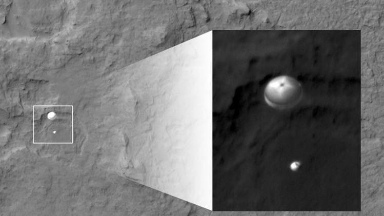 "In this image released by NASA/JPL-Caltech/Univ. of Arizona, NASA's Curiosity rover and its parachute, left, descend to the Martian surface on Sunday, Aug. 5, 2012. The high-resolution Imaging Science Experiment (HiRISE) camera captured this image of Curiosity while the orbiter was listening to transmissions from the rover. The inset image is a cutout of the rover stretched to avoid saturation. The rover is descending toward the etched plains just north of the sand dunes that fringe ""Mt. Sharp."" (AP Photo/NASA/JPL-Caltech/Univ. of Arizona)"