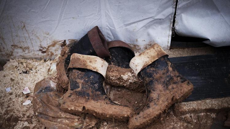 Muddy boots belonging to displaced Syrians are seen at the entrance of a tent in the Azaz camp for displaced persons north of Aleppo province, Syria, Monday, Feb. 18, 2013. According to Syrian activists the number of people in the Azaz camp has grown  by 3,000 in the last weeks due to heavier shelling by government forces. (AP Photo/Manu Brabo)