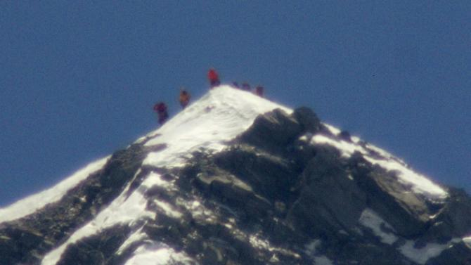 A team of climbers led by 80-year-old Japanese mountaineer Yuichiro Miura stand on the summit of Mount Everest on Thursday, May 23, 2013. Miura on Thursday became the oldest man to reach the top of Mount Everest, a Nepali official and Miura's Tokyo-based support team said. The photo was taken with a telephoto lens from an altitude of 5,550 meters (18,208 feet). It is not clear which of the climbers in the photo is Miura. (AP Photo/Kyodo News) JAPAN OUT, MANDATORY CREDIT