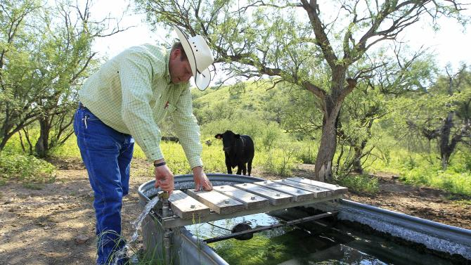 In this Friday, Aug. 10, 2012 photo, rancher Dan Bell, who owns a 35,000-acre cattle ranch along the border between the United States and Mexico, checks out part of his property in Nogales, Ariz., including a watering station for his cattle, which is also user-friendly for illegal immigrants that walk his land. (AP Photo/Ross D. Franklin)