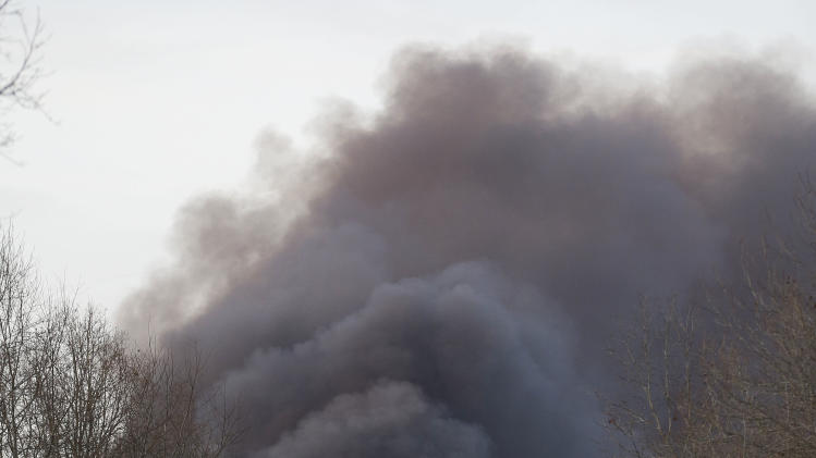 Smoke rises from a fire at a burning plastics recycling plant on a contaminated federal Superfund site on Wednesday, Dec. 18, 2013, near Lyles, Tenn. Officials evacuated area homes because they were concerned about toxic fumes. (AP Photo/Mark Humphrey)