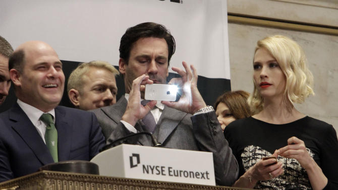 "Jon Hamm, center, is flanked by actress January Jones and Matthew Weiner, creator of AMC's ""Mad Men"" television show, as he takes a photo with his mobile phone during opening bell ceremonies at the New York Stock Exchange, Wednesday, March 21, 2012. The show is scheduled to premiere its new season Sunday, March 25.  (AP Photo/Richard Drew)"