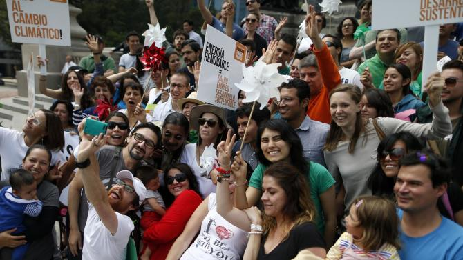 People pose for a selfie during a Climate Change march to demand politicians take tougher action to protect the climate at Angel de la Independencia monument in Mexico City