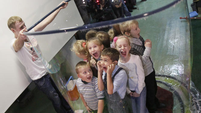 Children react as bubble is formed around them during Ukrainian record attepmt for the most people in a bubble, in Kiev