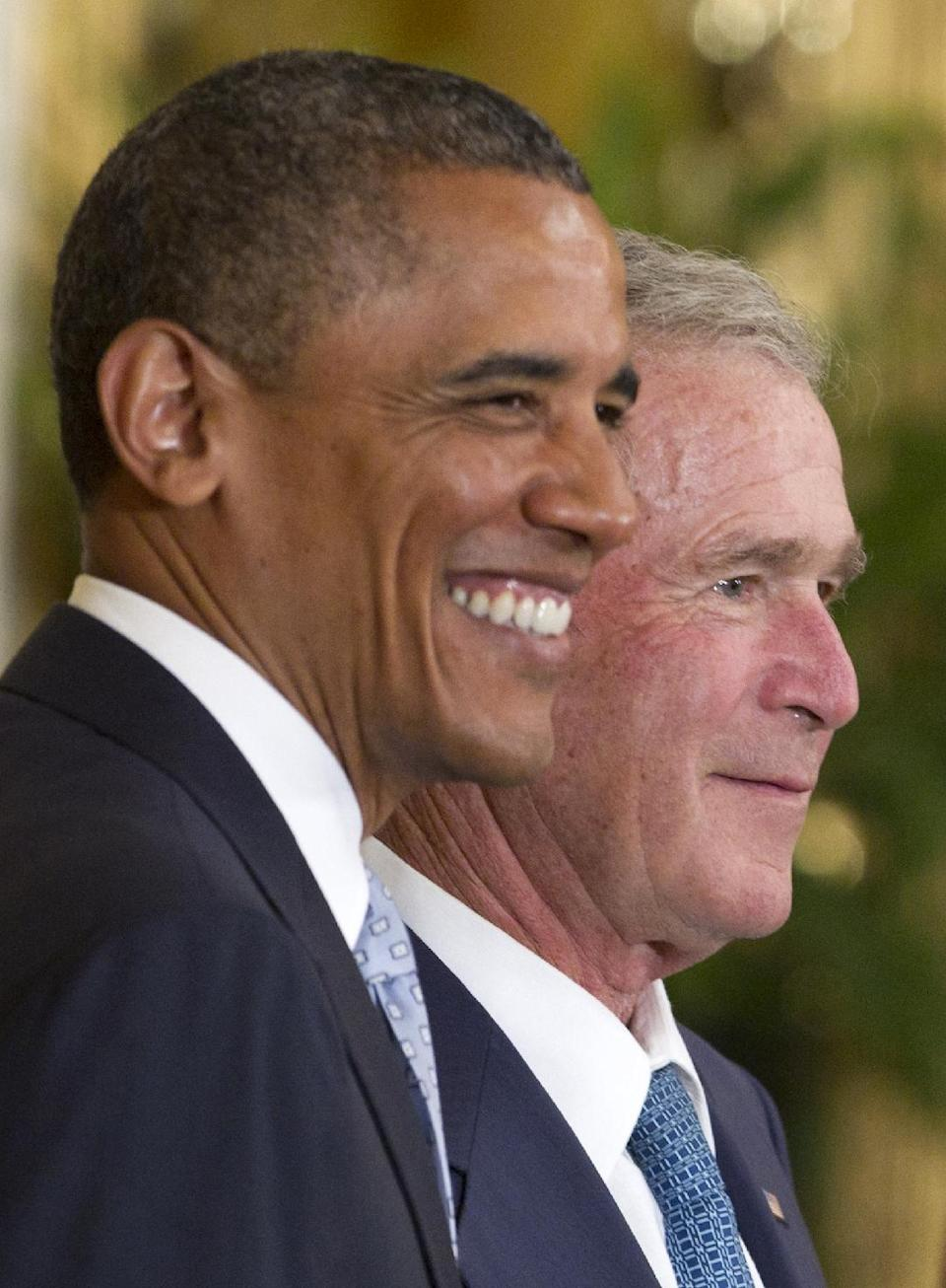 President Barack Obama stands with former President George W. Bush during a ceremony to unveil the Bush's portraits, Thursday, May 31, 2012,  in the East Room of the White House in Washington. (AP Photo/Carolyn Kaster)