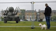 A man walks his dog past a Rapier missile defence system, which could play a role in providing air security during the Olympics, at Blackheath in southeast London on May 3, 2012. Britain is girding itself for the biggest peacetime security operation in its history featuring anti-aircraft missiles on rooftops and a warship in the River Thames for the London Olympics