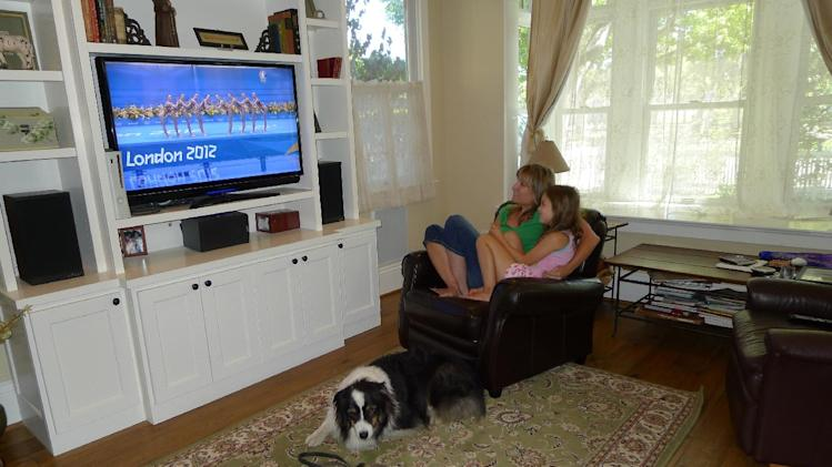 "Julie O'Grady watches the 2012 Olympics with her daughter Molly and dog Bosco Thursday Aug. 9, 2012 in her home in Palo Alto, Calif. If Bosco, Julie O'Grady's Australian shepherd in Palo Alto, Calif., could speak, he'd likely be shrieking, ""Get a grip woman!"" His pained, pathetic pleas haven't been enough to pry the tech industry public relations specialist away from the Olympics. Nearly eight in 10 Americans, have watched or followed the games either on television, online or via social networks, according to a survey done Aug. 2-5 by the Pew Research Center for the People & the Press. (AP Photo/Christian Fleury)"