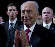 FILE - In this March 4, 2012 file photo, Israeli President Shimon Peres applauds in Washington. President Barack Obama and first lady Michelle Obama will honor a diverse cross-section of political and cultural icons — including former Secretary of State Madeleine Albright, astronaut John Glenn, basketball coach Pat Summitt and rock legend Bob Dylan — with the Medal of Freedom at a White House ceremony Tuesday. The Medal of Freedom is the nation's highest civilian honor. It's presented to individuals who have made especially meritorious contributions to the national interests of the United States, to world peace or to other significant endeavors. (AP Photo/Carolyn Kaster, File)
