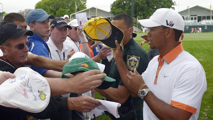 Tiger Woods, right, signs autographs for fans after finishing his weather-shortened round on the ninth green of the pro-am of the Arnold Palmer Invitational golf tournament in Orlando, Fla., Wednesday, March 20, 2013.(AP Photo/Phelan M. Ebenhack)