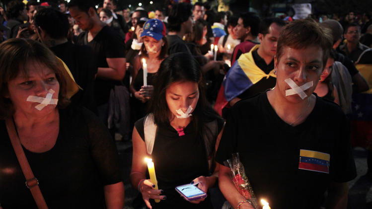 Demonstrators hold candles during a protest against the visit of Venezuela's President Nicolas Maduro to Santiago, Chile, Monday, March 10, 2014. Maduro is expected to travel to Chile to attend Tuesday's swearing-in of Michelle Bachelet as Chile's president. (AP Photo/Victor Ruiz Caballero)