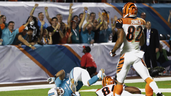 Miami Dolphins cornerback Brent Grimes scores a touchdown after Cincinnati Bengals quarterback Andy Dalton fumbled the ball during the second half of an NFL football game, Thursday, Oct. 31, 2013, in Miami Gardens, Fla. Bengals wide receiver Marvin Jones (82) and tight end Jermaine Gresham (84) are at right. (AP Photo/Lynne Sladky)