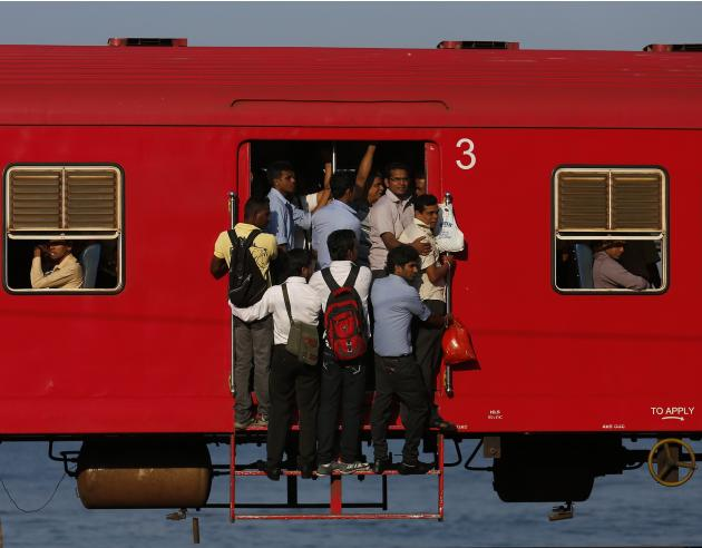 People hang onto a crowded local passenger train as they travel to Colombo