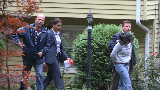 Annie Dookhan, right, is escorted to a cruiser outside her home in Franklin, Mass. Friday, Sept. 28, 2012. Dookhan is accused of faking drug results, forging signatures and mixing samples a state police lab.  State police say Dookhan tested more than 60,000 drug samples involving 34,000 defendants during her nine years at the lab. Defense lawyers and prosecutors are scrambling to figure out how to deal with the fallout. (AP Photo/Bizuayehu Tesfaye)