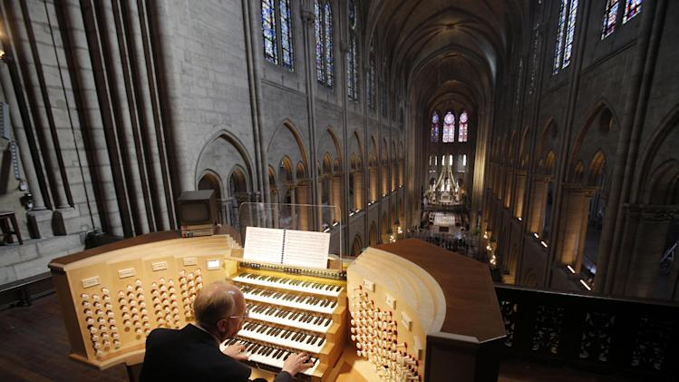 In this Thursday, May 2, 2013 photo, Philippe Lefebvre, 64, plays the organ at Notre Dame cathedral in Paris. Despite the advances in organ technology, Lefebvre feels the weight of history in his job. (AP Photo/Christophe Ena)