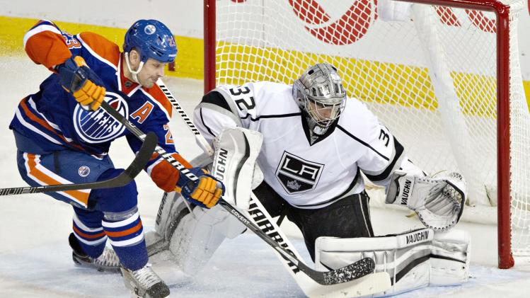 Los Angeles Kings goalie Jonathan Quick (32) makes the save on Edmonton Oilers Matt Hendricks (23) during second period NHL hockey action in Edmonton, Alberta, on Sunday March 9, 2014. (AP Photo/The Canadian Press, Jason Franson)