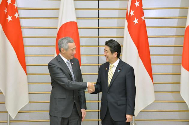 Singapore's PM Lee shakes hands with Japan's PM Abe in Tokyo