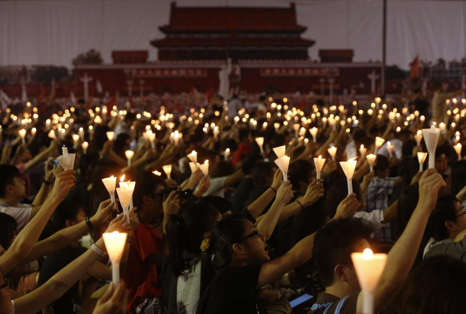 People hold up lit candles during a candlelight vigil at Hong Kong's Victoria Park Monday, June 4, 2012 to mark the 23rd anniversary of the Chinese military crackdown on the pro-democracy movement in Beijing. The background shows a picture taken from Beijing's Tiananmen Square in 1989. (AP Photo/Kin Cheung)