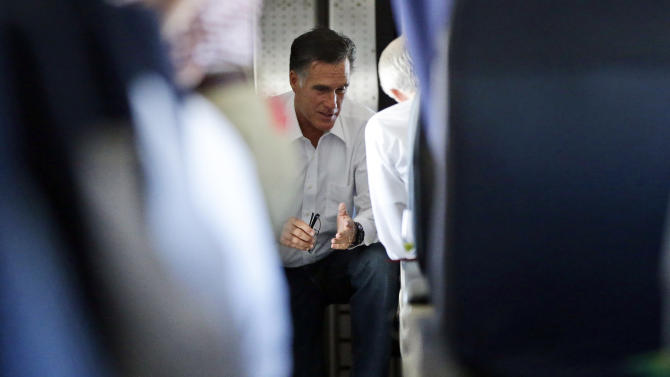 Republican presidential candidate and former Massachusetts Gov. Mitt Romney talks with Sen. Rob Portman, R-Ohio, who has also been his debate practice partner, on his campaign charter plane en route Denver, Monday, Oct. 1, 2012. (AP Photo/Charles Dharapak)