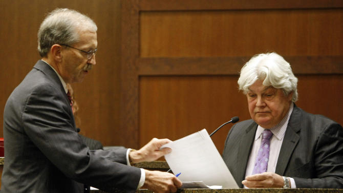"Defense attorney Robert Hoy presents medical records to Sanford Health Dr. Micheal Gonzales Tuesday, Nov. 20, 2012, during the trial of Dr. Jon Norberg in District Court at the Cass County Courthouse in Fargo, N.D. The case of a Fargo surgeon accused of drugging and sexually assaulting his wife went to a jury Tuesday after a prosecutor told the group on the ninth day of testimony it was a ""he said, she said"" issue. (AP Photo/The Forum, David Samson)"