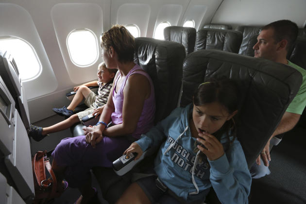 Zsuzsa Price, center, and her children Callum, 4, and Hailye, 10, ride in a JetBlue aircraft around JFK airport's tarmac, Saturday, Sept. 21, 2013 in New York. Dozens of families with children with au