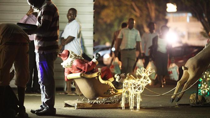 In this photo taken late Thursday Dec. 20, 2012, people walk past Christmas decorations at a shopping mall in Harare, Zimbabwe. Zimbabwe will join the rest of the world in celebrating the Christmas season in a manner that reflects its tradition and culture. Thousands of people are set to travel across the country to be with their families in rural areas. (AP Photo/Tsvangirayi Mukwazhi)