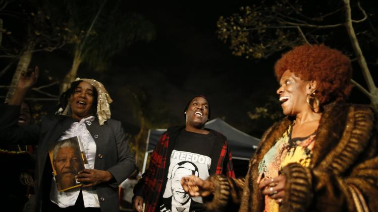 People dance at a candlelight vigil in memoriam of Nelson Mandela's death, in Los Angeles
