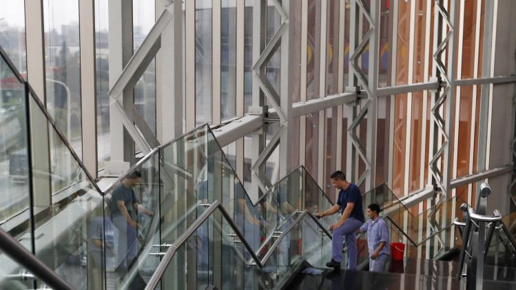 Workers clean glass panels inside a shopping mall in Buenos Aires