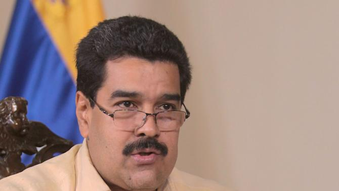 In this photo provided by Miraflores Presidential Press Office, Venezuela's Vice President Nicolas Maduro holds a miniature copy of Venezuela's constitution as he gives an interview on state television in Caracas, Venezuela, Friday, Jan. 4, 2013. Maduro said Friday that President Hugo Chavez could be sworn in by the Supreme Court later on if he's not able to take the oath of office before lawmakers on Jan. 10 because of his struggle with cancer, dismissing the argument by some opposition leaders that new elections must be called if Chavez doesn't take office as scheduled on Thursday. (AP Photo/Miraflores Presidential Office)