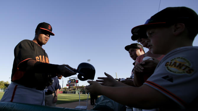 San Francisco Giants catcher Hector Sanchez signs autographs before a spring training baseball exhibition game against the Los Angeles Dodgers in Glendale, Ariz., on Friday, March 27, 2015. (AP Photo/Chris Carlson)