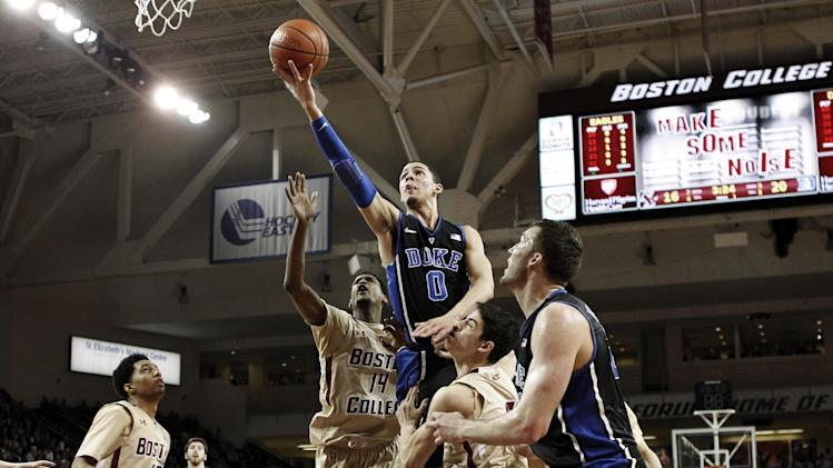 Duke guard Austin Rivers (0) shoots between Boston College's Matt Humphrey (14) and Danny Rubin (31) during the first half of an NCAA college basketball game in Boston, Sunday, Feb. 19, 2012. (AP Photo/Winslow Townson)
